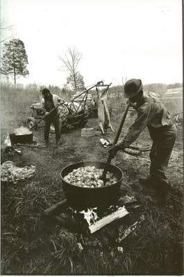 "Cooking up the lard and cracklin's in the old cast iron pots. Troy ""Spike"" Cunningham in the foreground and ""Boots"" Litchfield in the background. After the lard was cooked, Sarah Neighborgall remembers popping popcorn in the grease left in the kettles."
